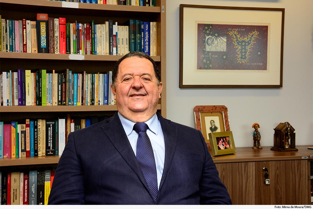 Magistrado sorri, sentado em gabinete, com livros ao fundo
