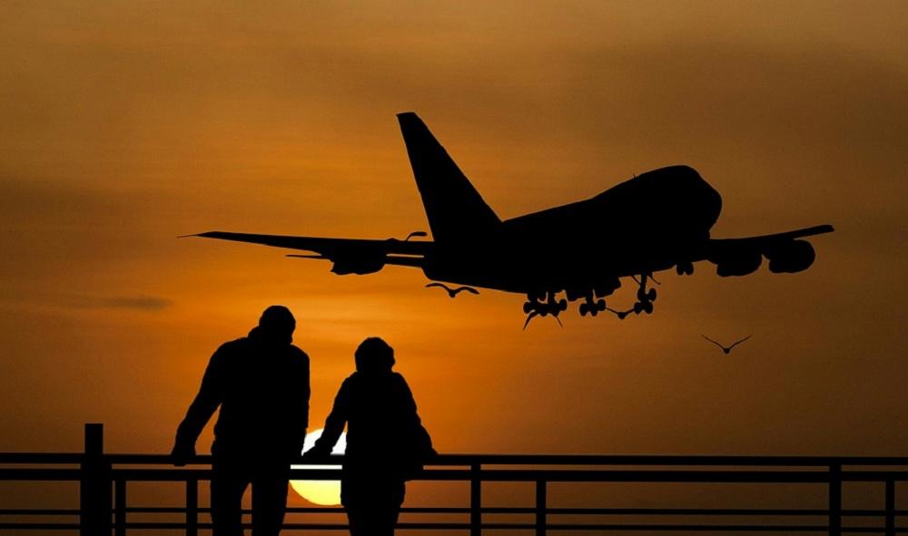 Um homem e uma mulher com avião decolando ao fundo