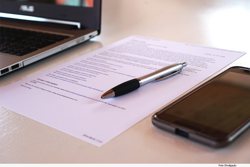 Contrato em papel sobre a mesa, com caneta e telefone ao lado