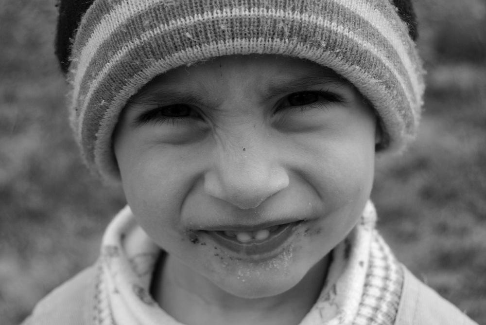 Rosto de criança de aproximadamente seis anos, de touca de lã