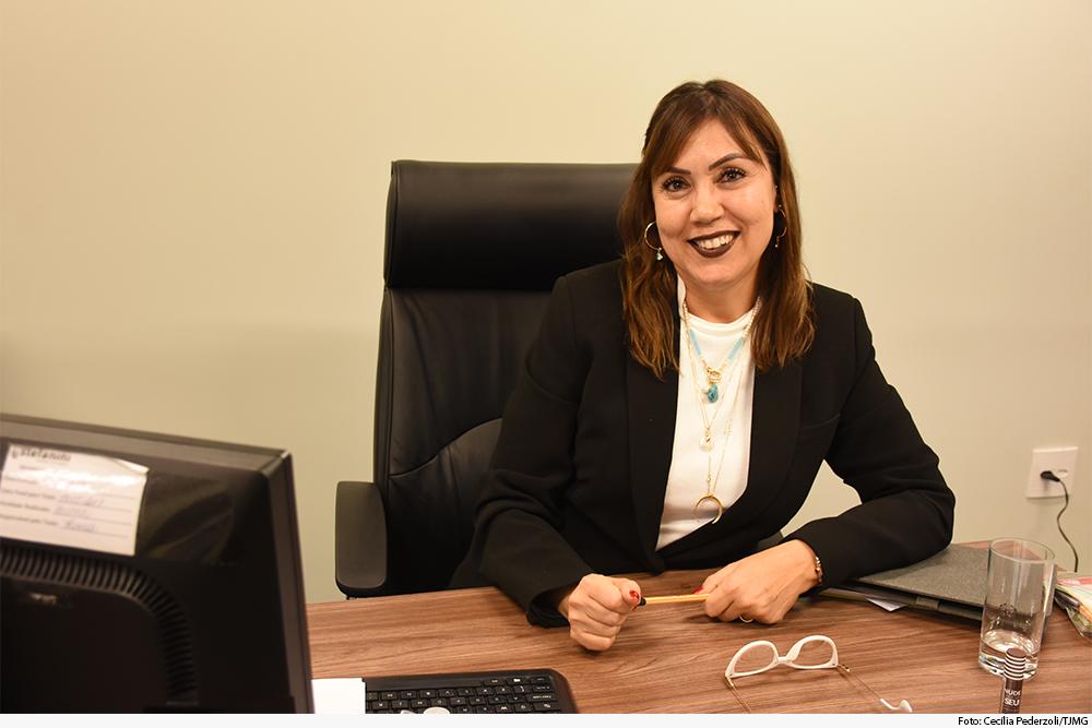 Magistrada sentada à mesa de trabalho, em gabinete