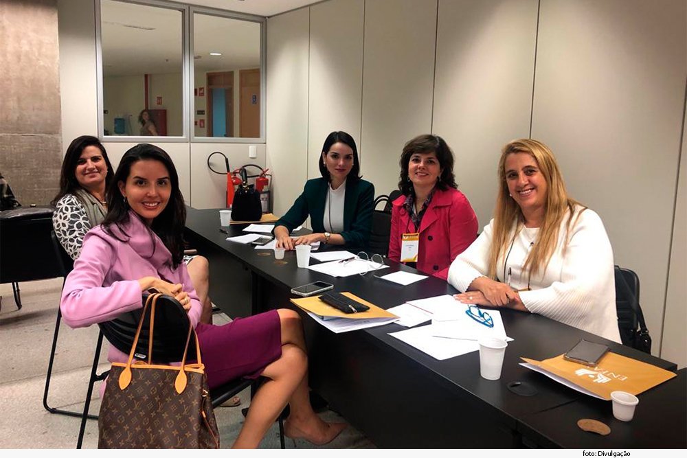 Magistradas assentadas à mesa participam de oficina