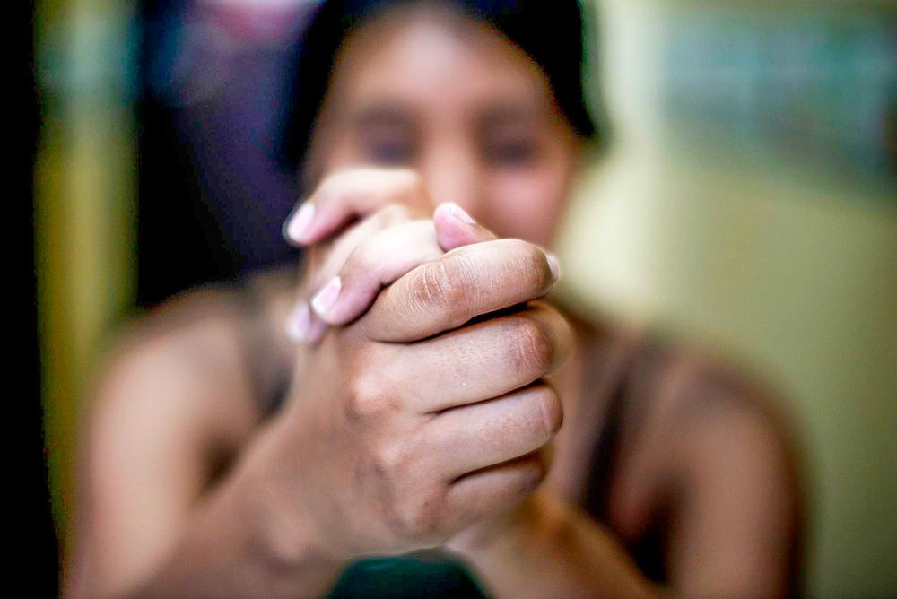 Mulher desfocada com os dedos entrelaçados em frente ao corpo