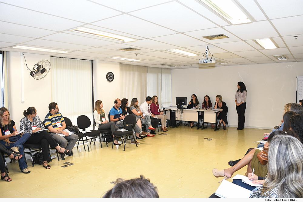 Sala de aula com pessoas sentadas em roda e instrutores de pé, à frente