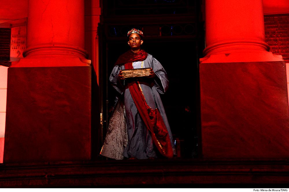 rapaz leva oferenda , vestido de rei