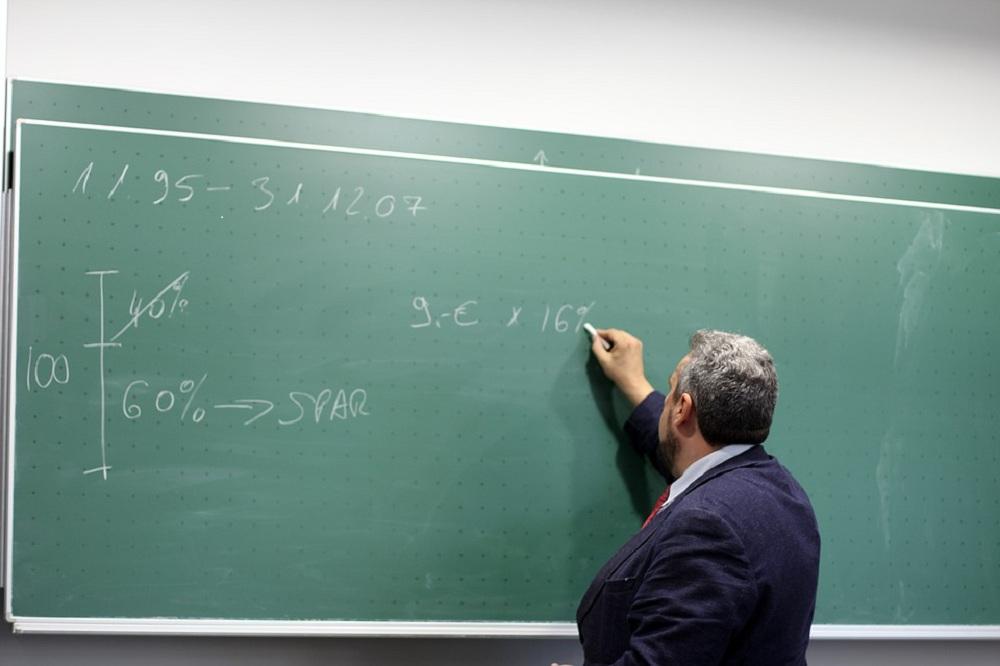 Homem de terno escreve em lousa com cálculos matemáticos