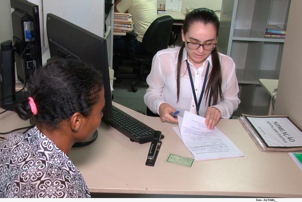 Foto mostra duas mulheres, uma delas conferindo um documento