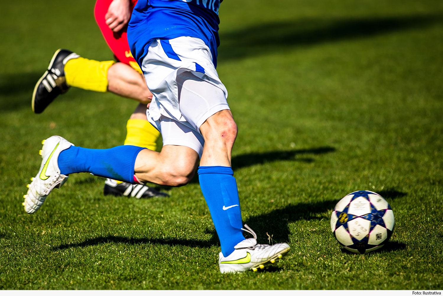 Plano mostrando pernas de jogadores chutando bola em campo de futebol