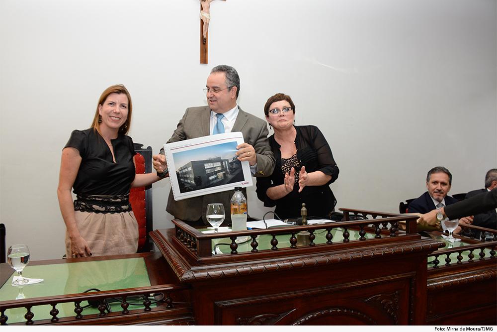 Foto mostra duas mulheres e um homem no meio segurando uma foto