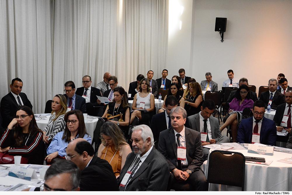 Público dividido em grupos (mesas) assiste a palestra