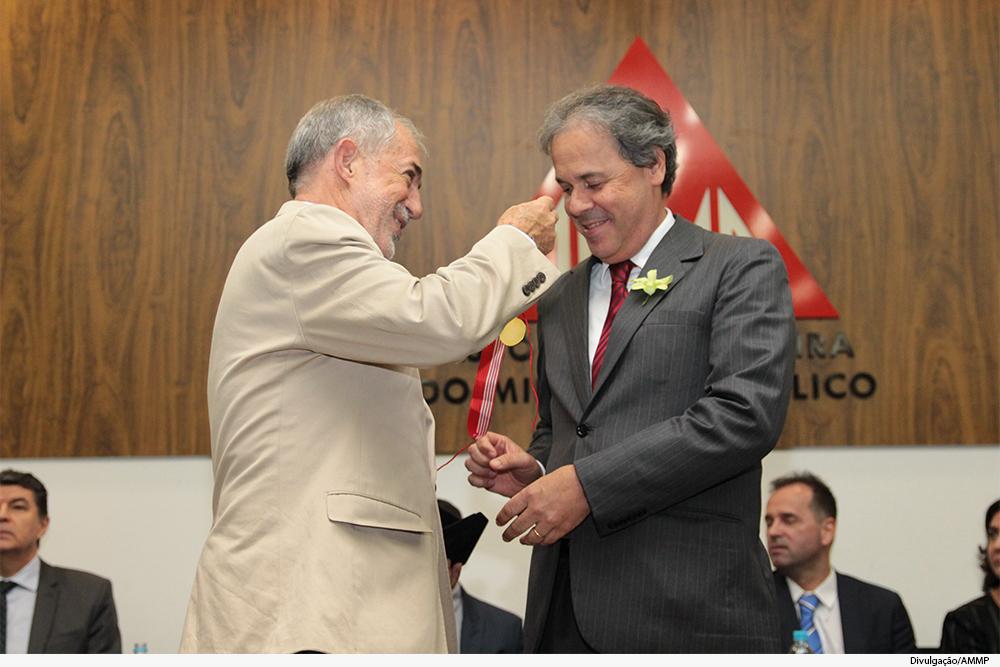 Homem coloca medalha em homenageado