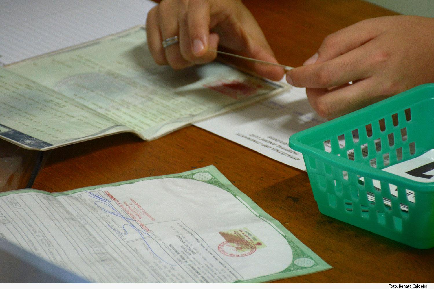Mão segurando carteira de identidade em cima de mesa com vários documentos e cesto de plástico verde