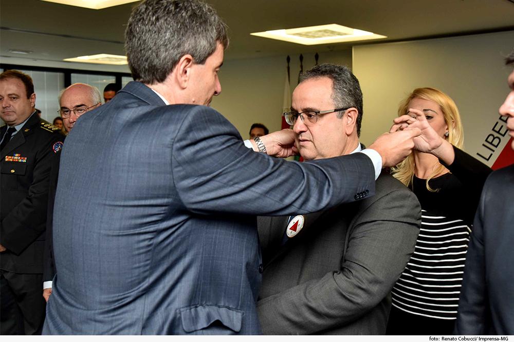 Homem coloca medalha no pescoço de outro