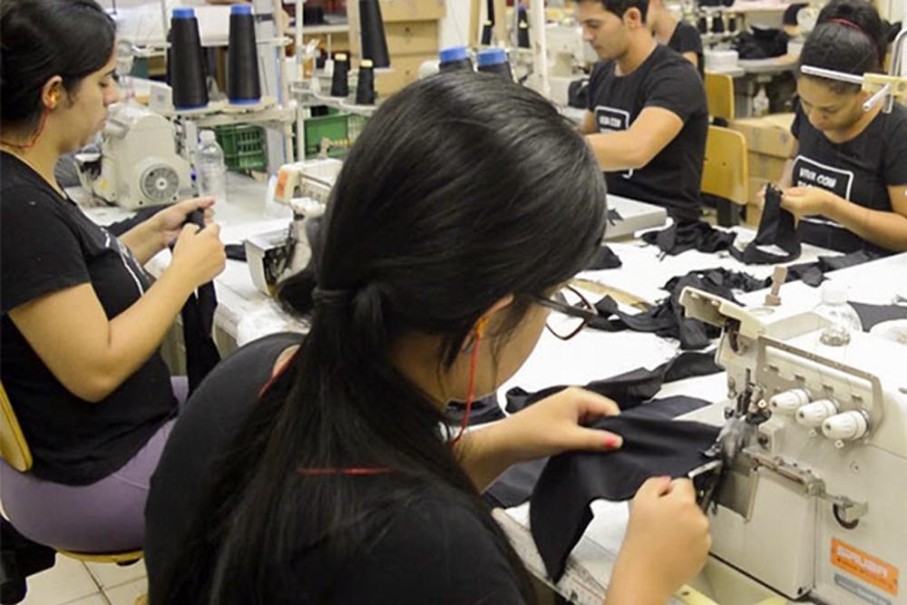 Pessoas manuseiam máquinas de costura em confecção