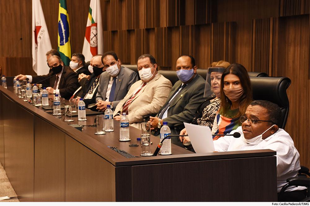 Mesa de honra com autoridades em que participante fala ao microfone