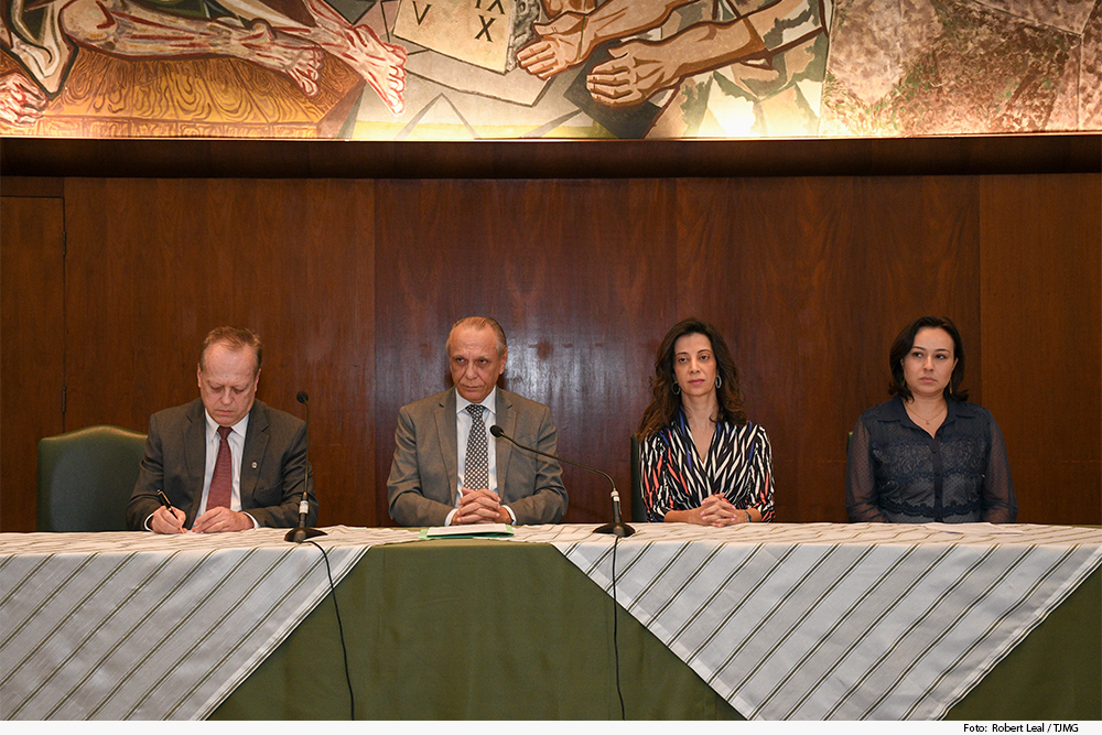 dois homens e duas mulheres em uma mesa de abertua de evento