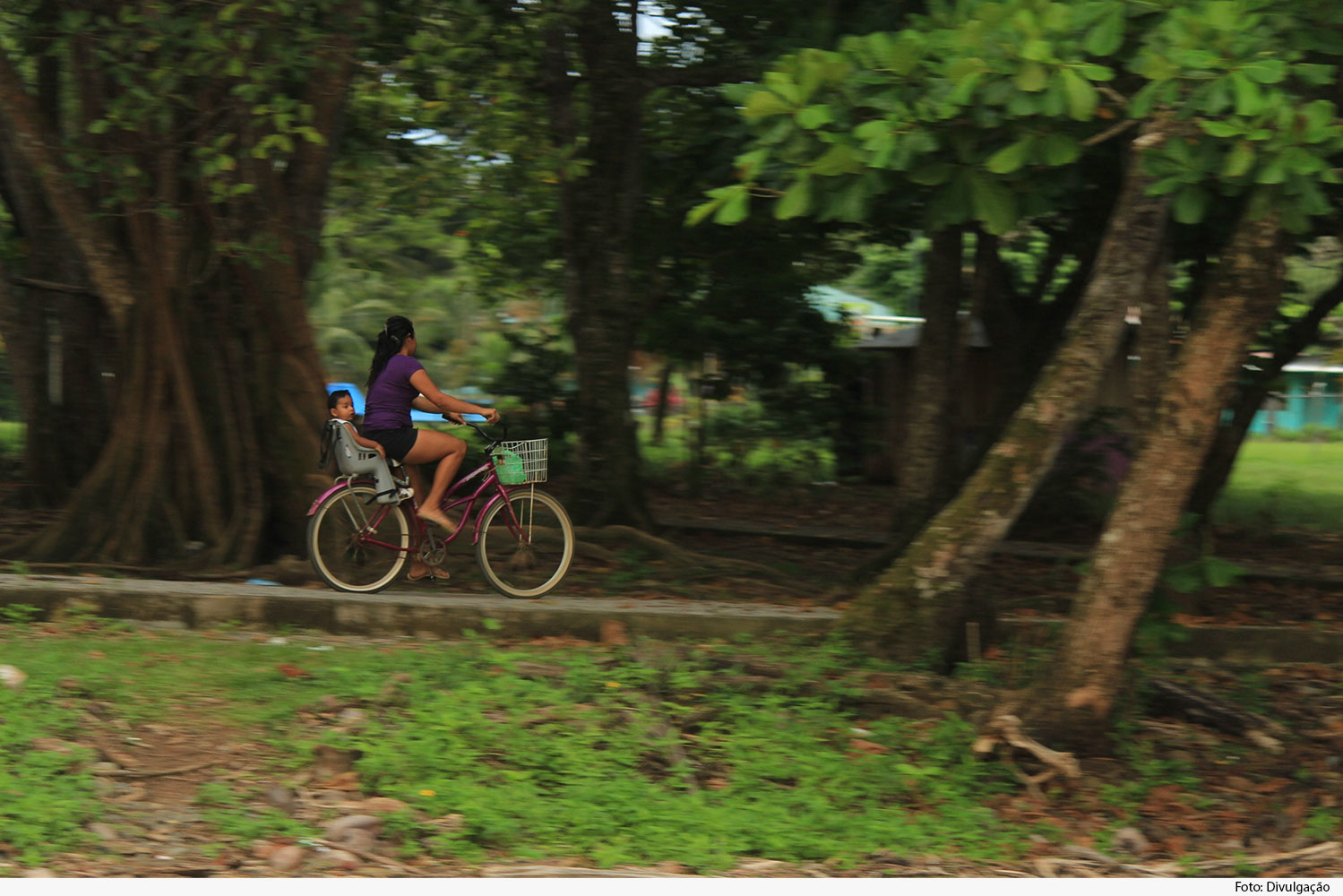Mulher em bicicleta com criança na garupa