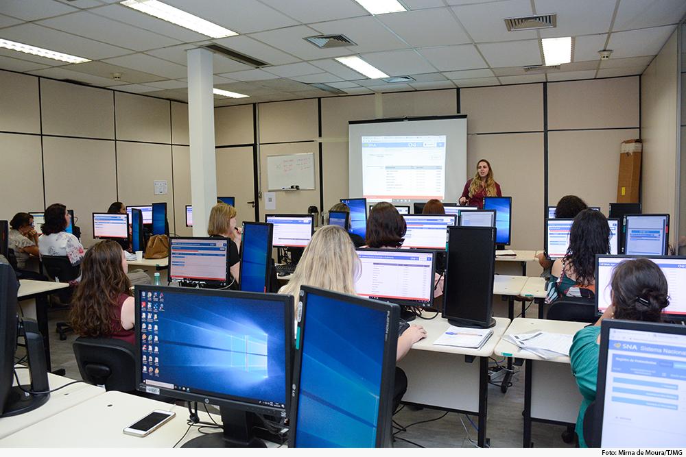 Pessoas fazem curso em laboratório de informática com palestrante de pé, à frente