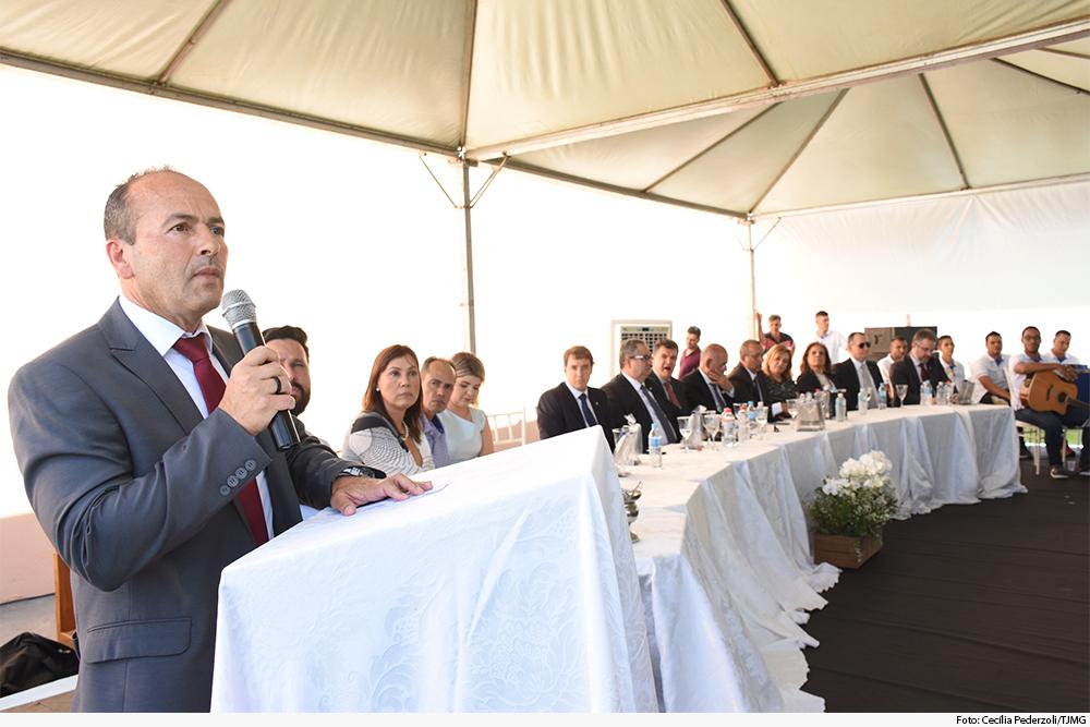 Homem fala ao microfone diante de uma mesa de honra com homens e mulheres sentados