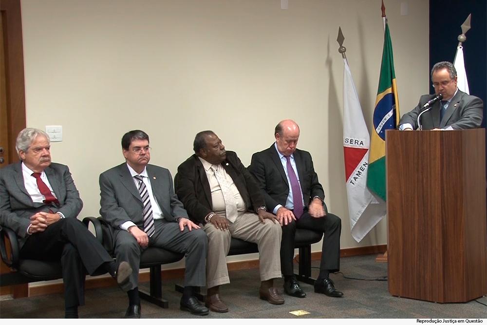 homem discursando em microfone e outros homens sentados
