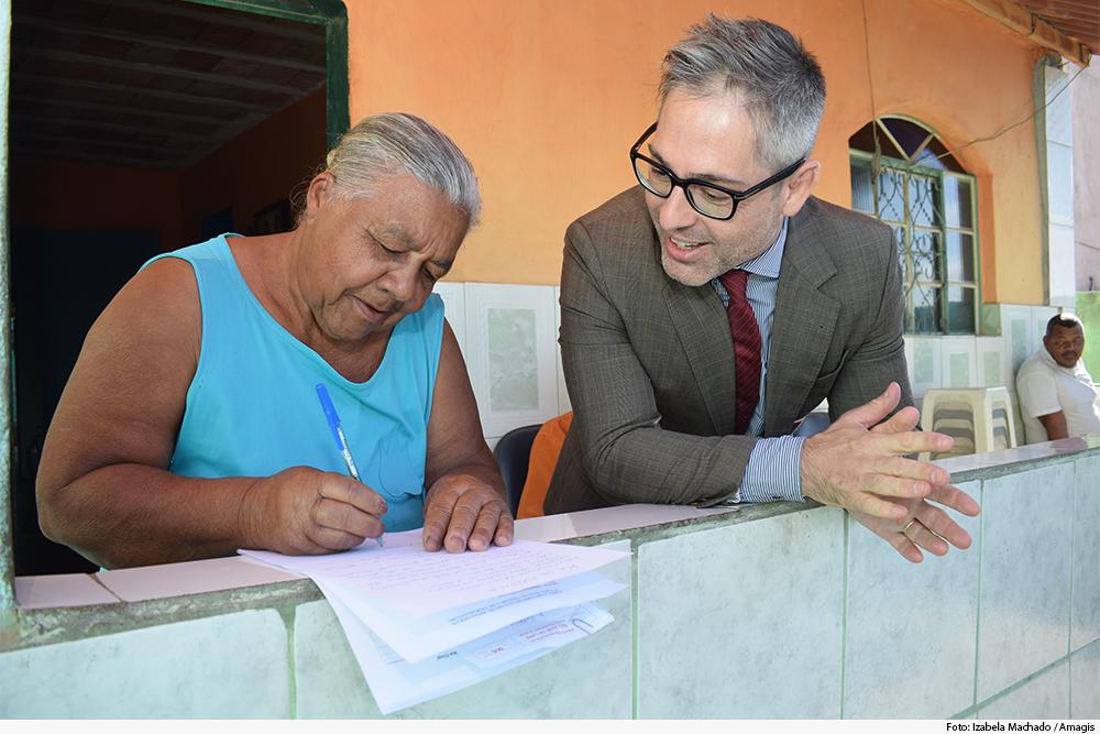 Juiz e idosa, encontados em parapeito, conversa enquanto ela assina documento