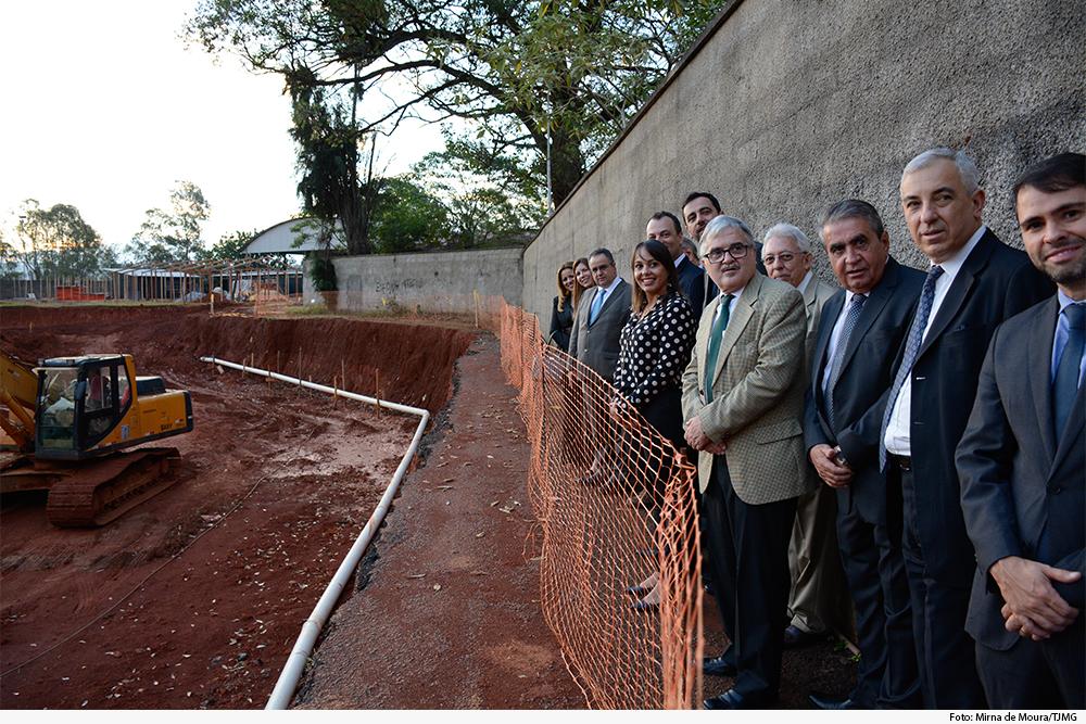 Foto mostra terreno com trator, muro com pessoas encostadas nele