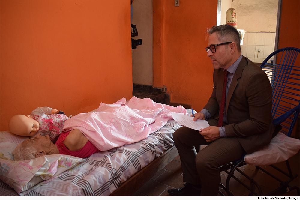 Juiz sentado em cadeira próxima a cama em que dorme idosa com boneca