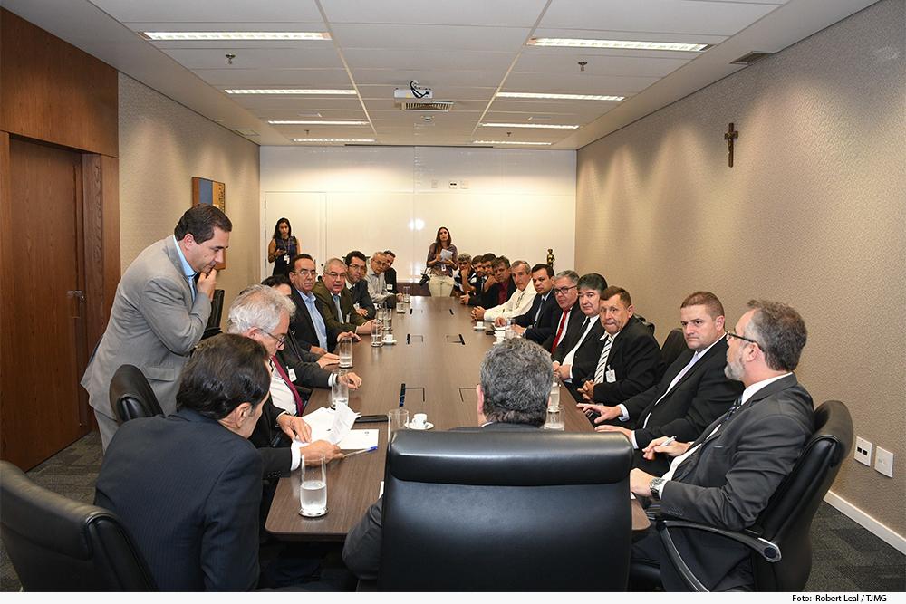 Grupo de prefeitos em mesa de reunião