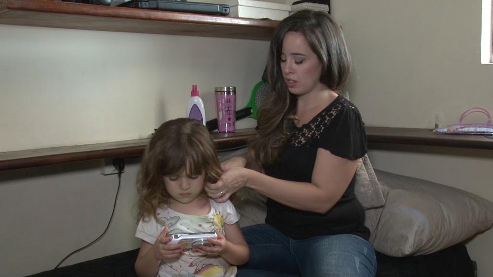 Mãe penteia cabelo de criança que brinca ao celular