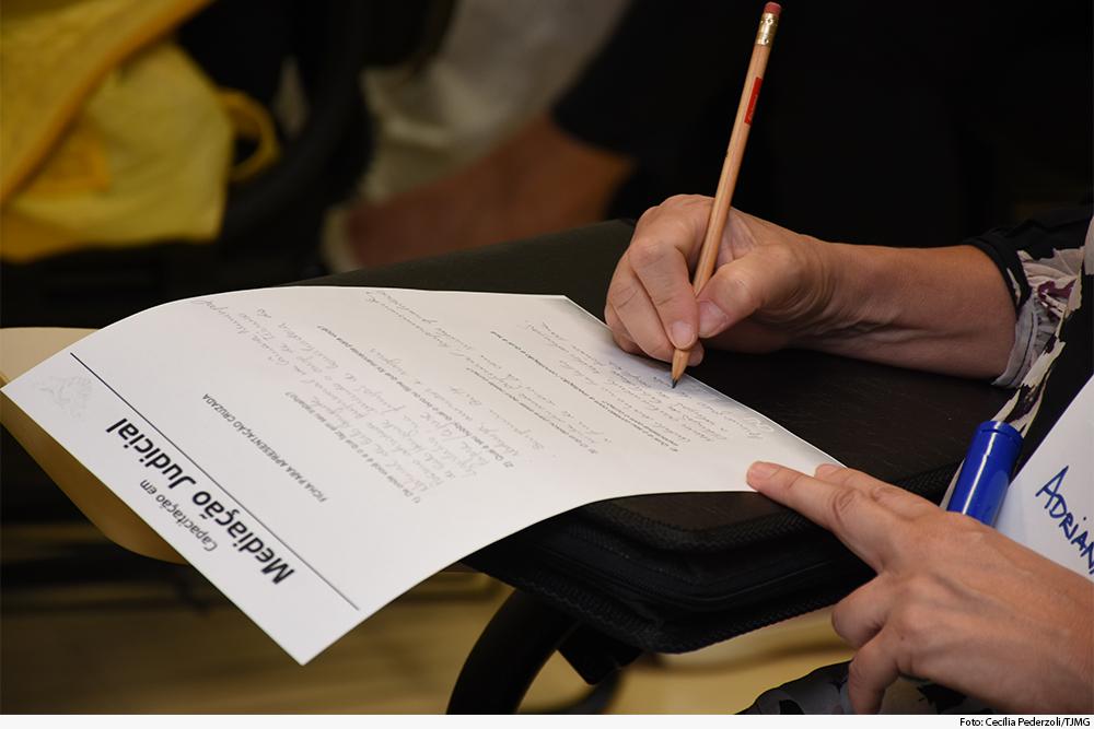 Mão segurando lápis anota em folha de papel com logomarca da Ejef