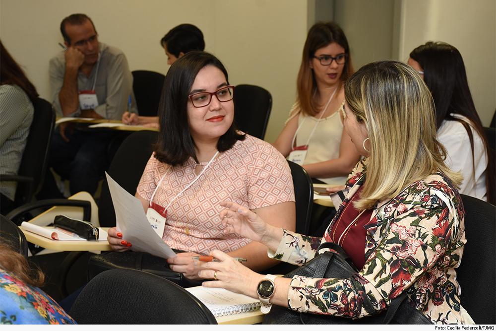 Participantes do curso, sentados, em sala de aula, interagem