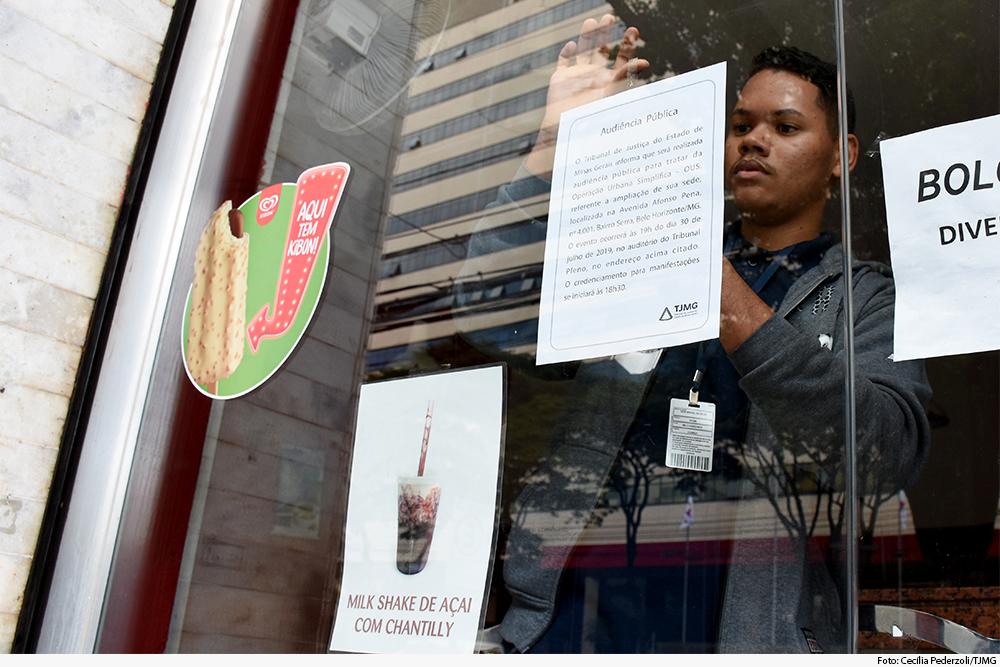 Rapaz cola cartaz em vidro de fachada de loja